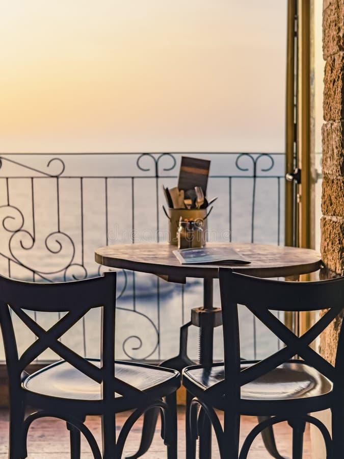 Tabla en un café enfrente de la ventana abierta que pasa por alto el mar teniendo en cuenta puesta del sol imagen de archivo