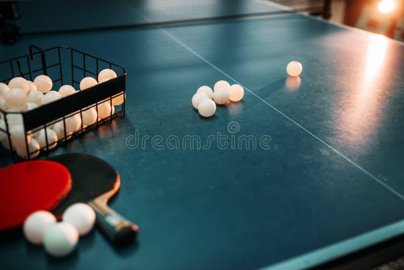 Tabla, estafas y cesta de ping-pong con las bolas foto de archivo libre de regalías