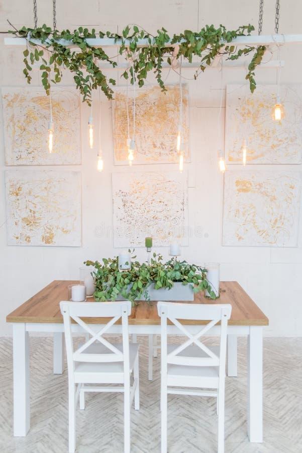 Tabla festiva adornada con la guirnalda del eucalipto de las ramas en el centro y las velas Guirnaldas retras de la tabla de la N fotos de archivo libres de regalías