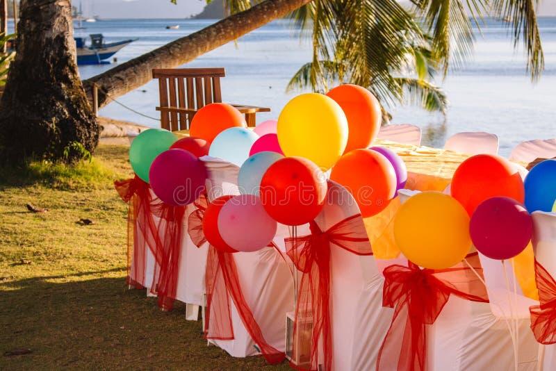 Tabla festiva con los globos coloridos en fondo de la playa con la palmera y el barco Concepto de la celebración del feliz cumple fotografía de archivo libre de regalías