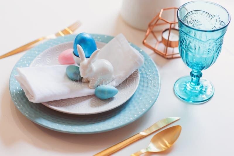 Tabla festiva de Pascua y de la primavera adornada en colores rosados y azules con los cubiertos metálicos de oro modernos foto de archivo