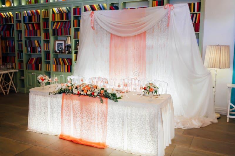 Tabla festiva para la novia y el novio adornados con las luces, el paño, y las flores imagen de archivo libre de regalías
