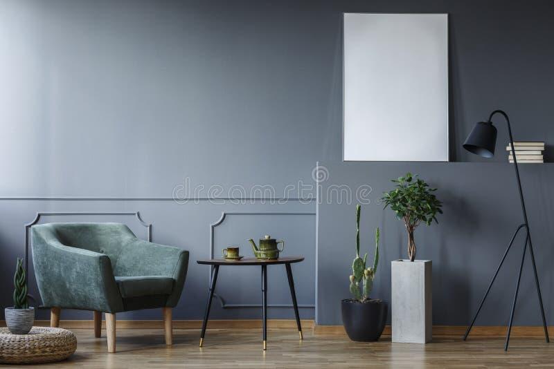 Tabla negra entre la butaca y las plantas verdes en el interior gris w imagenes de archivo