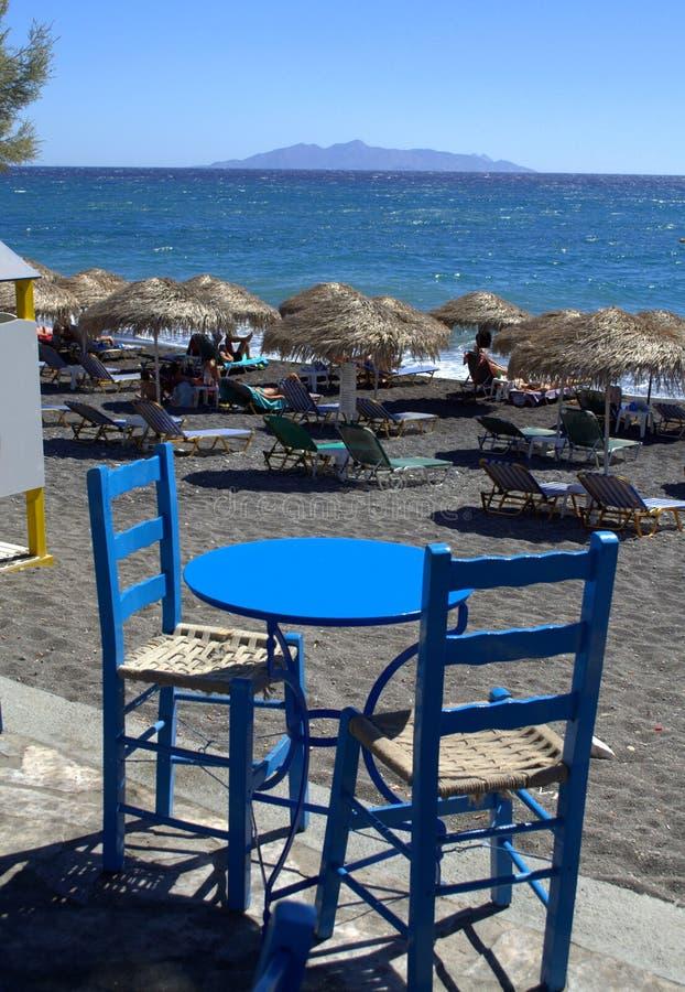 Tabla para dos en la playa negra de la arena, Santorini imágenes de archivo libres de regalías