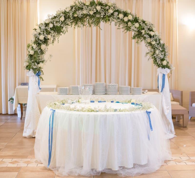 Tabla para el pastel de bodas con el arco de la flor imagen de archivo libre de regalías