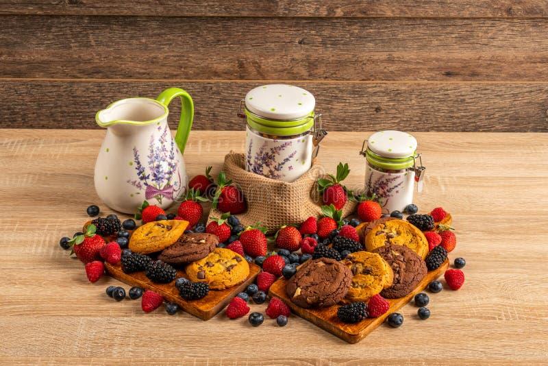 Tabla por completo de frambuesas, de frutas del bosque y de galletas del chocolate foto de archivo libre de regalías