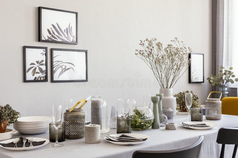 Tabla puesta con los vidrios y las flores del champán en un interior moderno del comedor imagenes de archivo
