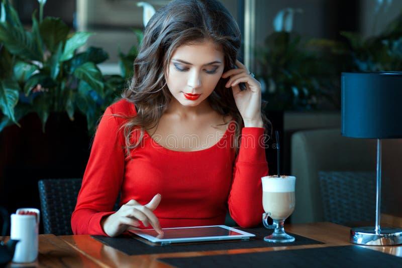 Tabla que se sienta del café de la muchacha y trabajo para la ordenador-tableta fotos de archivo
