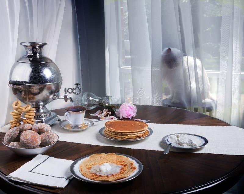 Tabla rusa con el samovar, las crepes, la crema agria y el té caliente Gato siberiano que se sienta detrás de una cortina y que m imagen de archivo libre de regalías