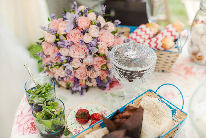 Tabla servida al aire libre Centro de flores con lavanda y rosas fotos de archivo