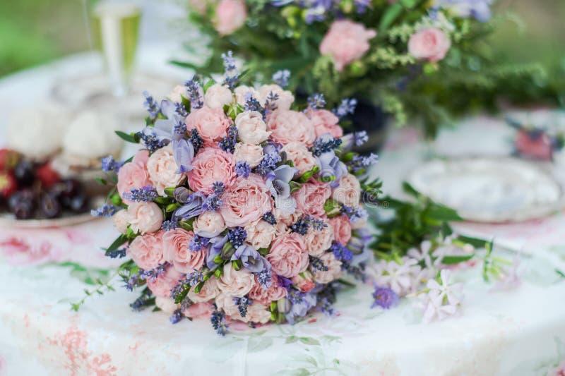 Tabla servida al aire libre Centro de flores con lavanda y rosas fotografía de archivo