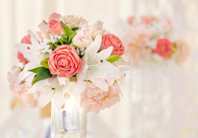 Tabla servida para la cena del evento, adornada con las composiciones florales en floreros en sombras rosadas y coralinas Ramo de imagen de archivo libre de regalías