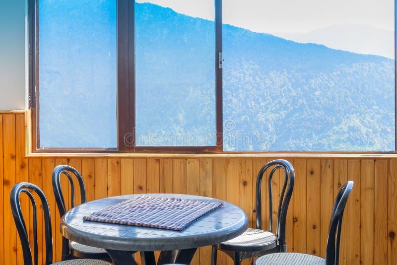 Tabla, sillas y ventana con la vista de la montaña afuera fotografía de archivo
