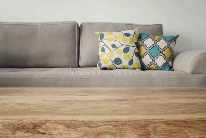 Tabla vacía de madera delante del interior del sofá de la sala de estar fotografía de archivo libre de regalías