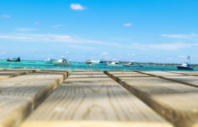 Tabla vacía del tablero de madera delante del mar azul, yates fotografía de archivo libre de regalías