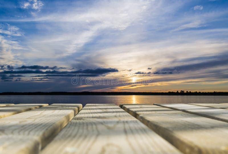Tabla vacía del tablero de madera delante del mar de la puesta del sol y del fondo del cielo Piso de madera de la perspectiva sob imagenes de archivo