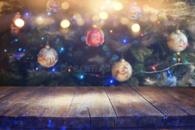Tabla vacía delante del árbol de navidad con el fondo de las decoraciones para el montaje de la exhibición del producto fotos de archivo libres de regalías