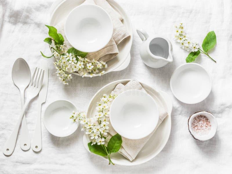 Tabla vacía servida con la loza blanca, flores, servilletas en el fondo blanco, visión superior Tabla casera acogedora de la comi fotos de archivo