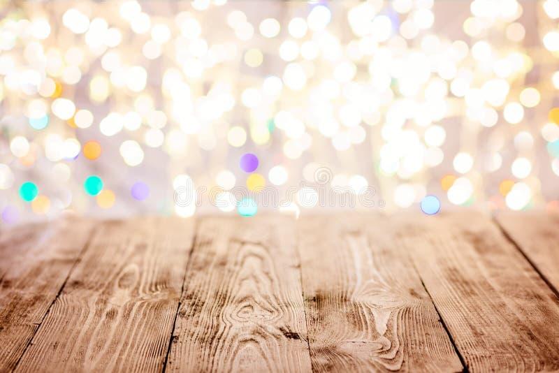 Tabla vacía vieja con las luces de la Navidad en el fondo imagenes de archivo