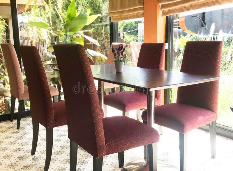 Tabla vacía y silla suave roja en restaurante o cafetería - adentro imagenes de archivo