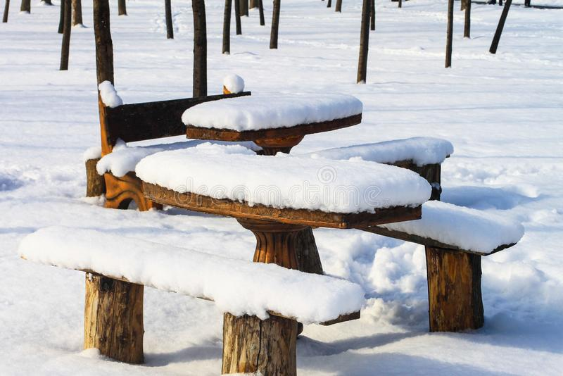 Tabla y banco de madera del vintage en el parque, cubierto con la nieve fresca blanca, invierno foto de archivo libre de regalías