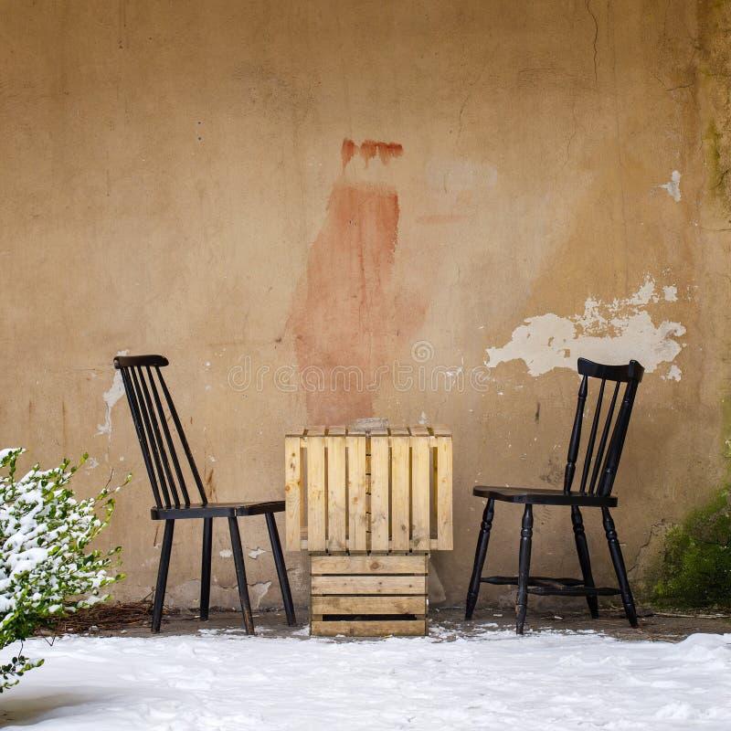 Tabla y dos sillas cerca de la pared imagenes de archivo