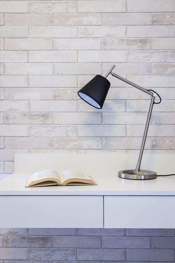 Tabla y libro de funcionamiento con la lámpara en fondo de la pared fotos de archivo