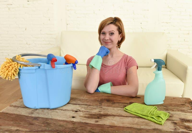 Tabla y muebles felices y alegres de la sala de estar de la limpieza de la mujer o del ama de casa con el paño fotografía de archivo