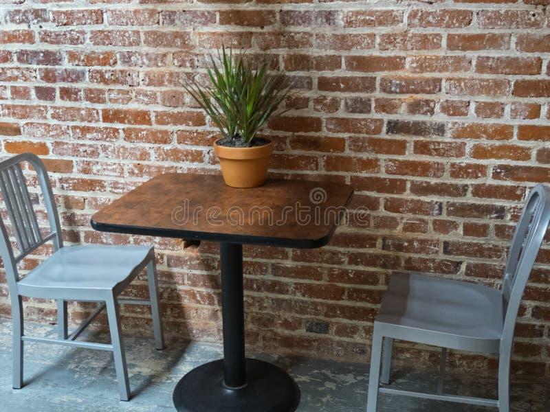 Tabla y sillas contra una pared de ladrillo foto de archivo libre de regalías