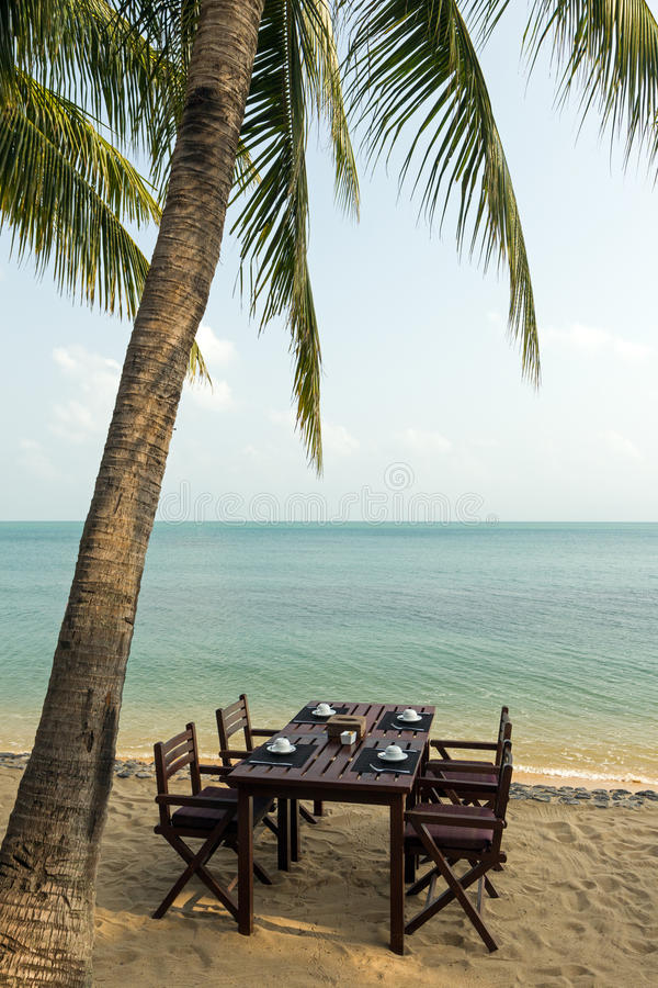 Tabla y sillas debajo de una palmera en una playa fotos de archivo libres de regalías