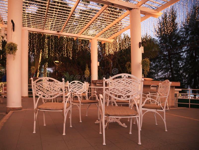 Tabla y sillas exteriores al aire libre blancas de la fiesta de jardín del parque con el techo ligero caliente de la decoración d fotografía de archivo libre de regalías