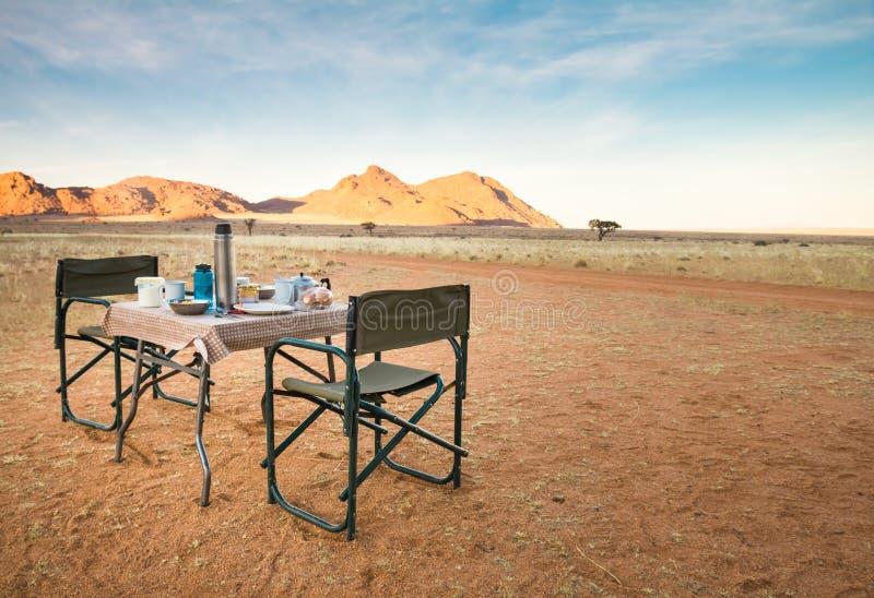 Tabla y sillas que acampan en el desierto Gran visión Salida del sol fotos de archivo