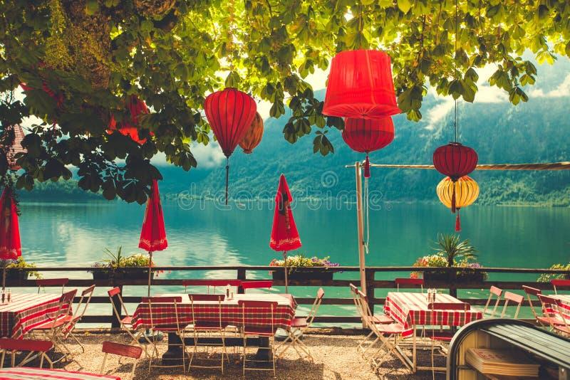 Tablas del café por el lago Hallstadt en Austria imagen de archivo libre de regalías