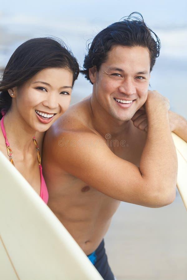 Tablas hawaianas asiáticas de los pares de la mujer del hombre en la playa foto de archivo