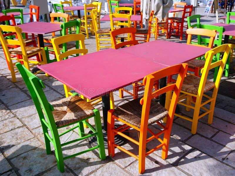 Tablas y sillas coloridas, Grecia del café imágenes de archivo libres de regalías