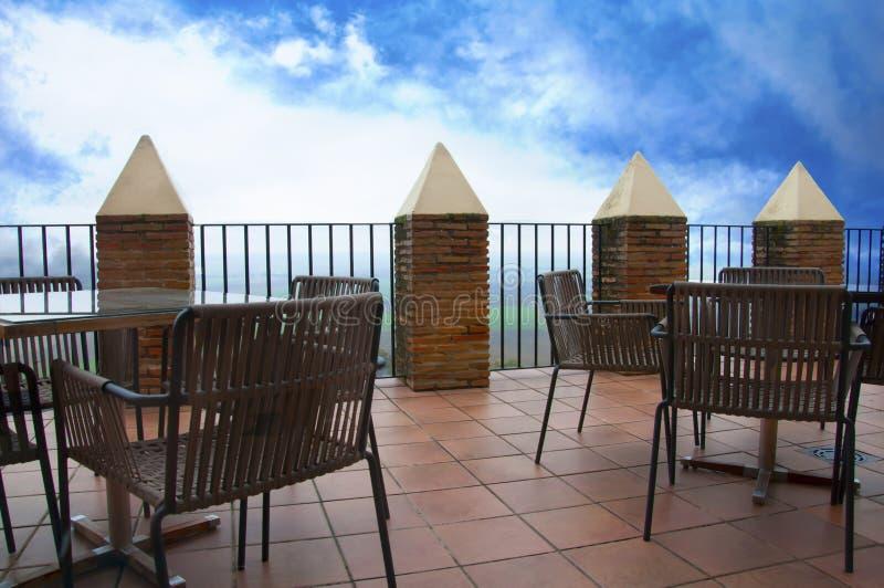 Tablas y sillas de madera en la terraza grande, cielo azul fotos de archivo libres de regalías