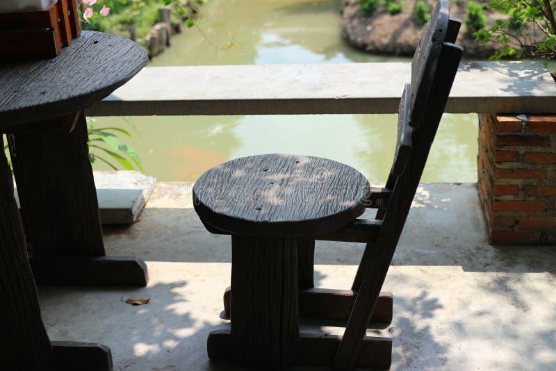 Tablas y sillas de madera viejas, estilo del vintage, esquina de sentada en un jardín asiático del estilo imágenes de archivo libres de regalías