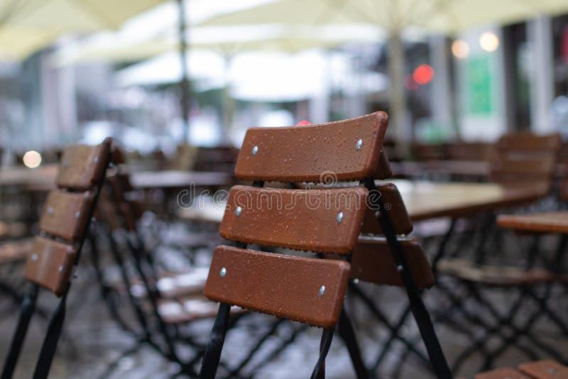 Tablas y sillas del restaurante bajo la lluvia imágenes de archivo libres de regalías