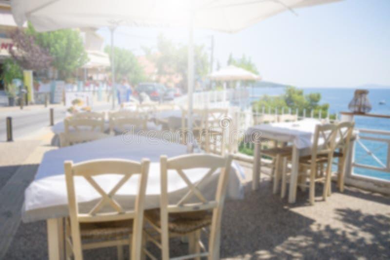 Tablas y sillas del restaurante debajo de la sombrilla en la terraza en la costa Escena borrosa del restaurante en los marmaras d foto de archivo