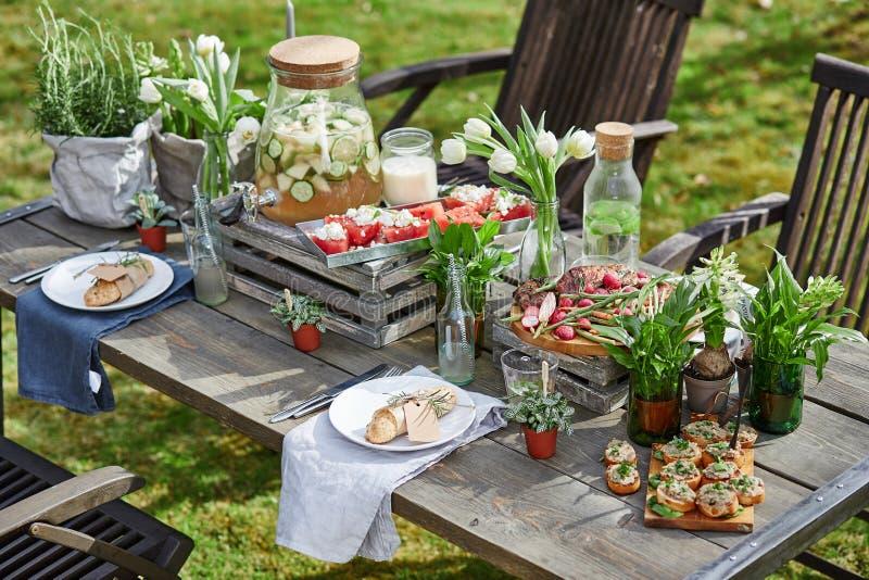 Table étendue avec des pains grillés, la viande grillée, pain de son, pastèque et photos libres de droits