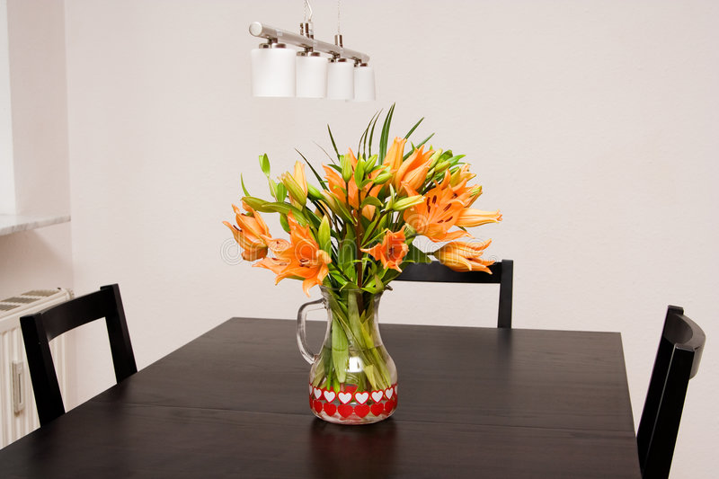 Table. Lilies in the vase on the dining table royalty free stock photos