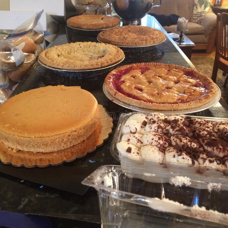 Holiday spread of pumpkin, apple pies and pumpkin cheesecake stock photography