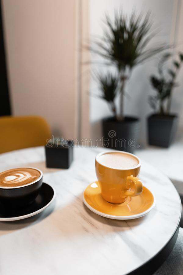 On the table in a beautiful vintage cafe is a black cup with a hot latte and a yellow cappuccino mug. Morning coffee break. In a gourmet cafe. Rest with a royalty free stock images
