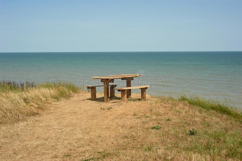 Table with benches on a cliff near the sea. Camping and wild recreation.Picnic in nature on the coast. royalty free stock image