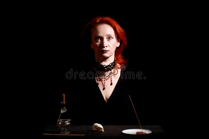 Fine emotional redhead witch with magical decorations and live expressions. Table with bird skull, candles and lamp. Black wizard background royalty free stock photos