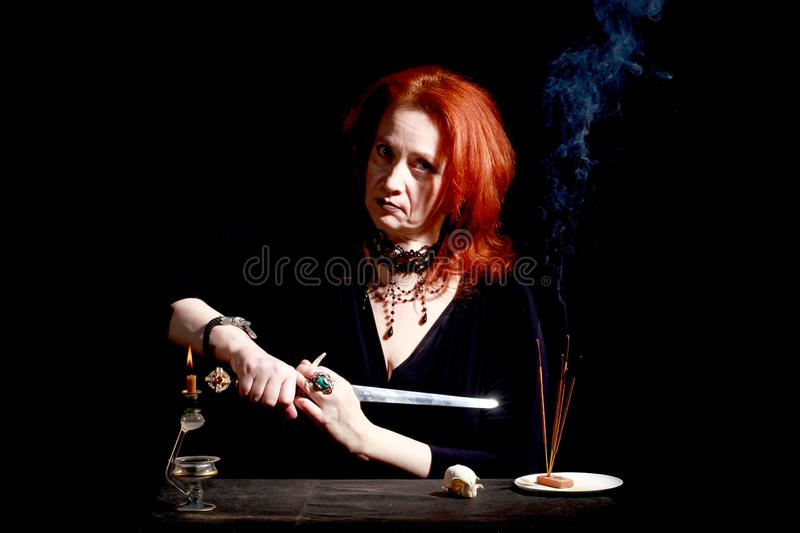 Witch with wizard stiletto. Fine emotional redhead witch with magical decorations and live expressions. Table with bird skull, candles and lamp. Black wizard stock images