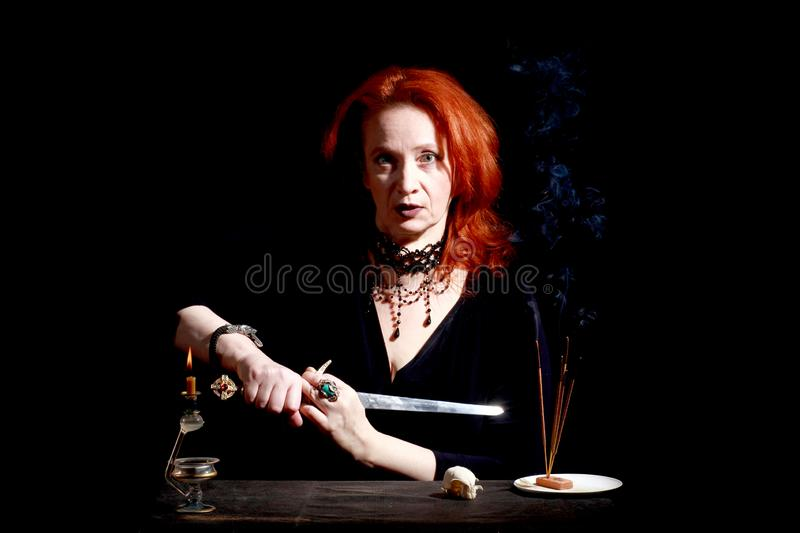 Witch with wizard stiletto. Fine emotional redhead witch with magical decorations and live expressions. Table with bird skull, candles and lamp. Black wizard royalty free stock images