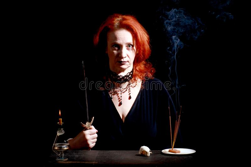 Witch with wizard stiletto. Fine emotional redhead witch with magical decorations and live expressions. Table with bird skull, candles and lamp. Black wizard stock photo