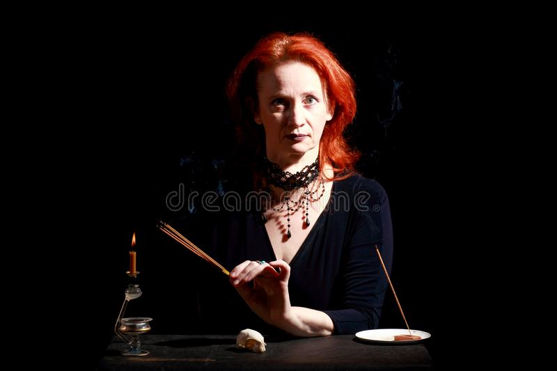 Witch light wizard candles. Fine emotional redhead witch with magical decorations and live expressions. Table with bird skull, candles and lamp. Black wizard royalty free stock image