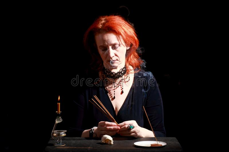 Witch light wizard candles. Fine emotional redhead witch with magical decorations and live expressions. Table with bird skull, candles and lamp. Black wizard royalty free stock photo